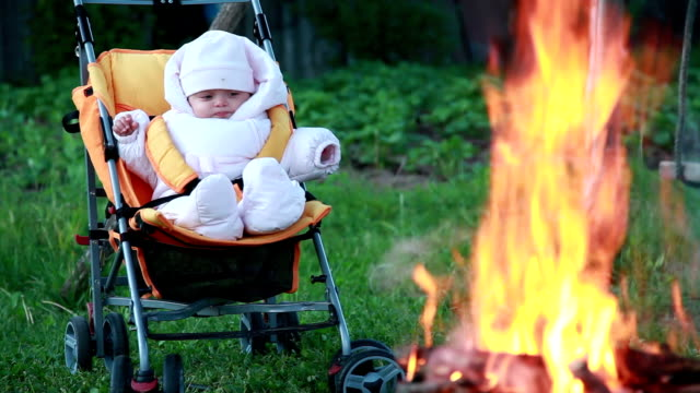 Baby sitting in the pram in front of the campfire video