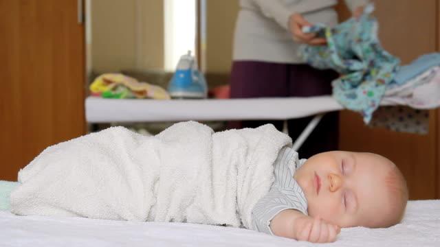 vidéos et rushes de sommeil de bébé et maman est fer à repasser. - allongé sur le dos
