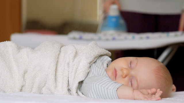 彼女の母親をアイロンしながらベッドで眠っている赤ちゃん。 - 家の雑用点の映像素材/bロール