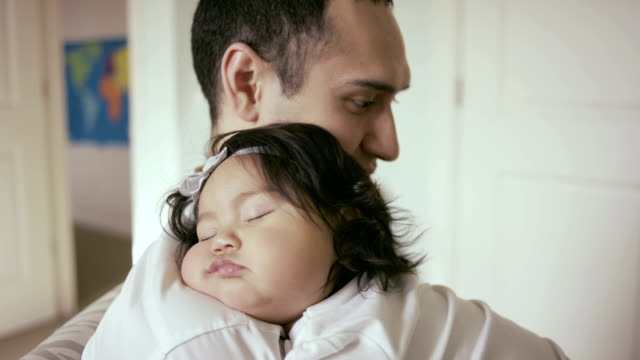 Baby sleeping on father in nursery video