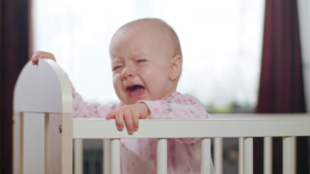 Baby Standing in a Crib at Home. Crying video