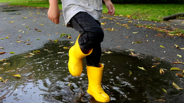Baby stomping through puddles in yellow rubber boots Baby boy stomping through puddles in yellow rubber boots stamping feet stock videos & royalty-free footage