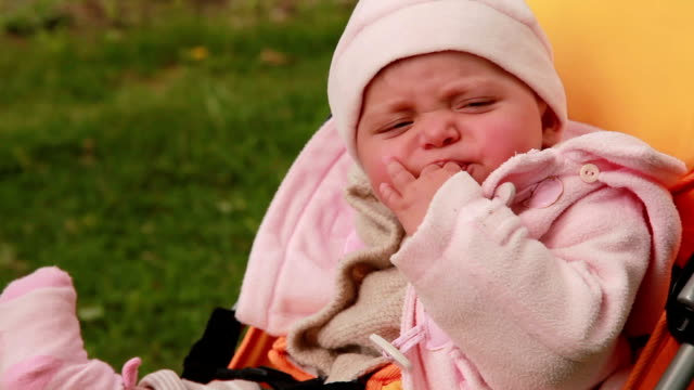 Baby sucking her fingers and falling asleep in the pram video