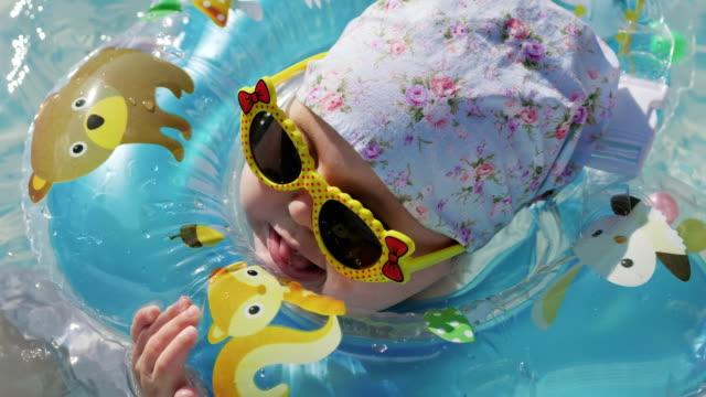 yüzme boyun yüzmek yüzüklü bebeğim - durgun su stok videoları ve detay görüntü çekimi