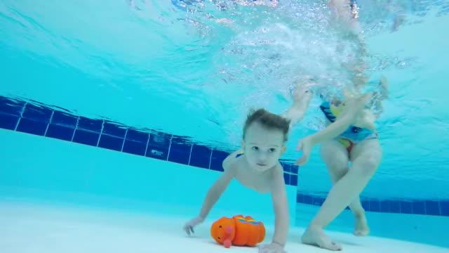 stockvideo's en b-roll-footage met baby neemt een speeltje van de bodem van het zwembad, close-up. - video's van baby