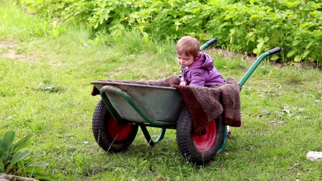 Baby taking out a ball from the wheelbarrow