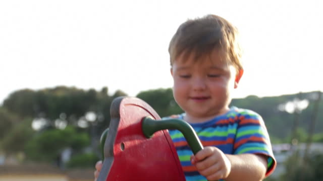 Baby Toddler in the Park Spring Bouncer at dusk video