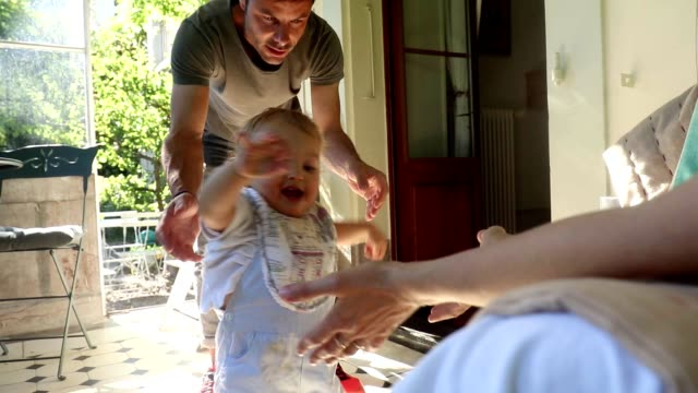 Baby toddler learning to walk with the help of parents. Mother incentivizing baby son to walk towards. Family moment together at family home balcony video