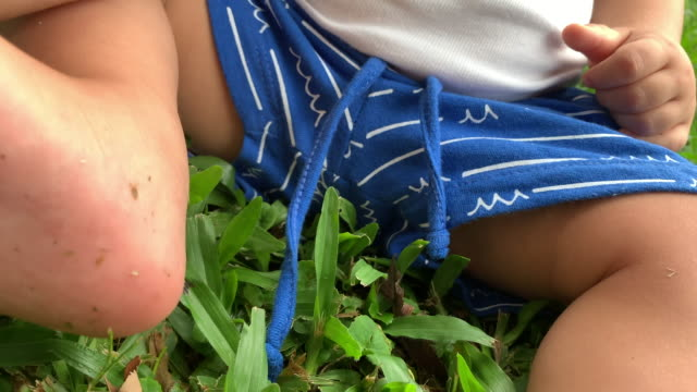 Baby toddler outside on grass holding feet and toes