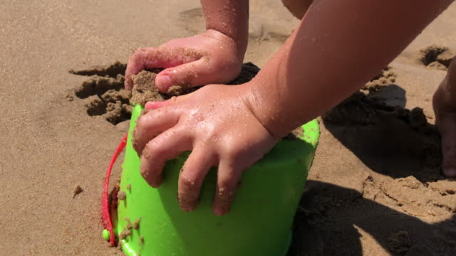 baby toddler playing with sand and bucket at the beach - solo bambini maschi video stock e b–roll