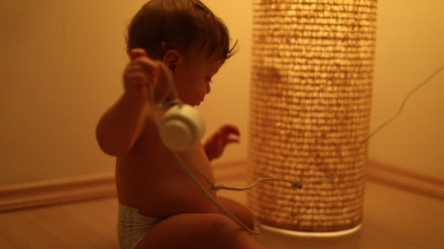 Baby toddler playing withlamp object at night. Infant plays by himself