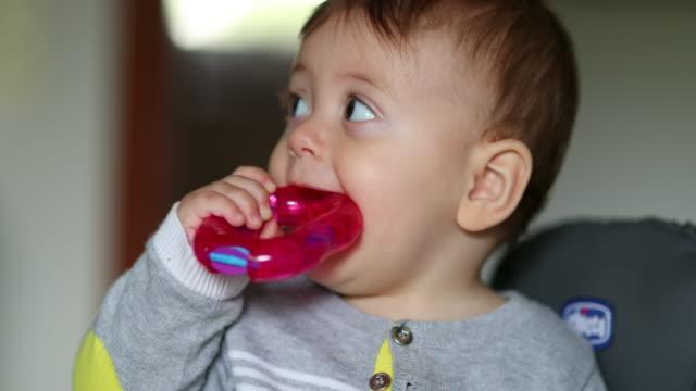 stockvideo's en b-roll-footage met de peuter die van de baby speelgoed in mond zet. zuigeling tandjesgroei - baby toy