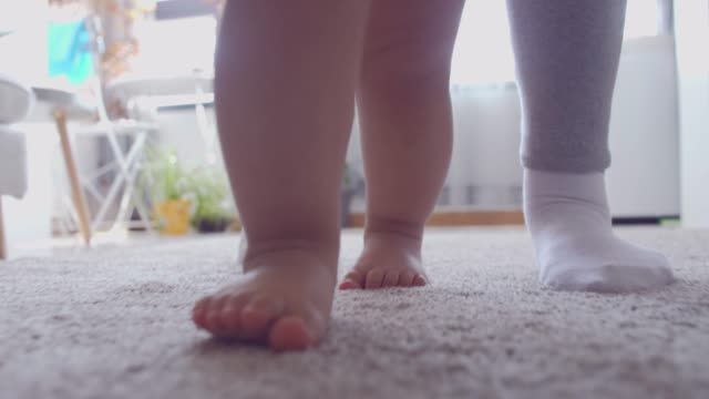 Baby walking supported by his mother