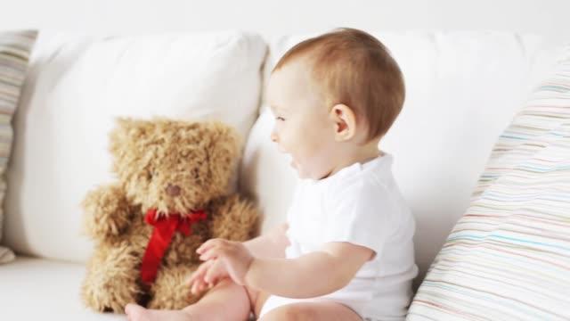 vídeos de stock e filmes b-roll de baby with teddy bear sitting on sofa at home - teddy bear