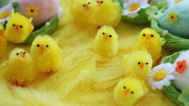 赤ちゃんの黄色のイースター玩具雛と羽の背景に卵。お祝いビデオ グリーティング カード ビデオ