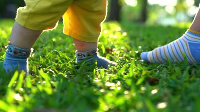 vídeos y material grabado en eventos de stock de primeros pasos del bebé en la hierba. los primeros pasos independientes. - principios
