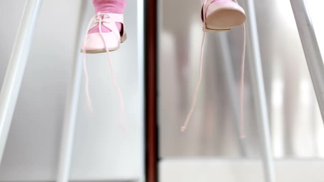Baby's legs Baby's legs sitting in child seat. Pink ballerinas. Child is waving legs. Kitchen. Fridge in the background. Locked down. Close shot. 50mm baby booties stock videos & royalty-free footage