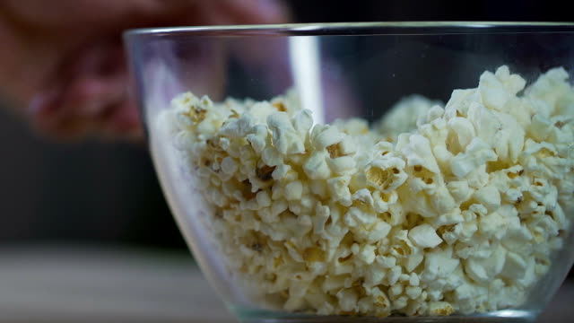 Bachelor is getting ready to watch football match, eating popcorn from the bowl video