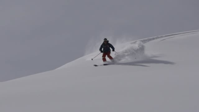Back country skiers descending mountain, deep powder snow video