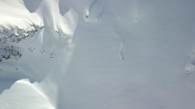 back country skiers descending mountain, deep powder snow - sci sci e snowboard video stock e b–roll