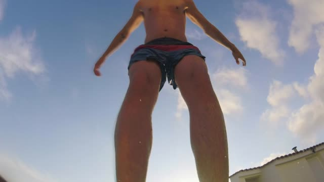 Back Flip Into Swimming Pool A close-up low angle view of a young caucasian man standing poolside at a holiday villa, he is wearing swimming shorts and he backflips into the swimming pool. swimwear stock videos & royalty-free footage