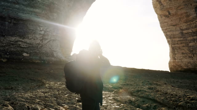 Back lit happy male photographer taking pictures of stunning rocky Normandy cliffs at sunny Etretat seaside slow motion.