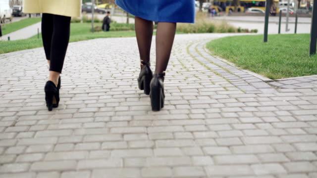 tillbaka ser ben av två flickor i rockar gående på trottoaren fullhd - gå tillsammans bildbanksvideor och videomaterial från bakom kulisserna
