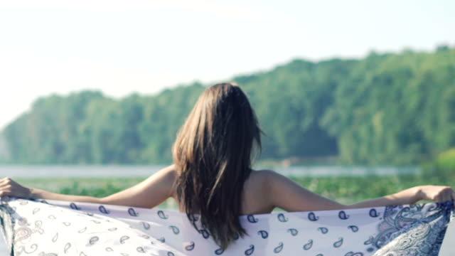 tillbaka blick av kvinna håller sarong i floden i vinden. slow motion - sarong bildbanksvideor och videomaterial från bakom kulisserna