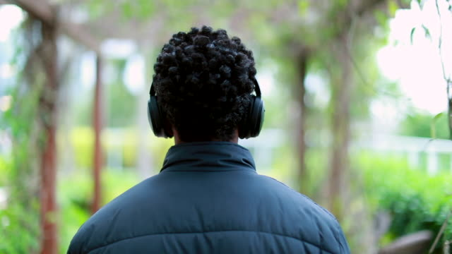 Back of black guy listening to music, podcast, or audiobook on headphones outside
