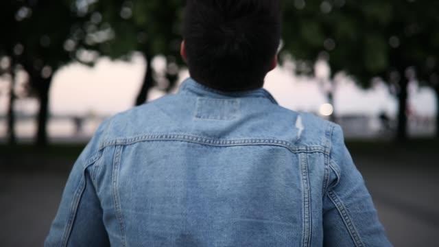 baksidan av man i trasiga jeansjacka promenader i stadsparken - jeans bildbanksvideor och videomaterial från bakom kulisserna