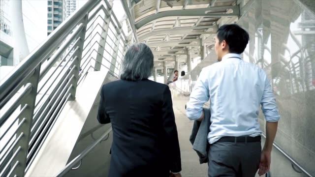 back of senior business manager and young business man walking and going to work over urban city background - podążać za czynność ruchowa filmów i materiałów b-roll