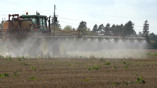 vidéos et rushes de retour de l'engrais de propagation de véhicule sur un champ de ferme de chaume de maïs. 4k - herbicide