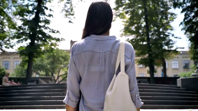 back of young college student going to university, walking upstairs in park with trees - dorsale video stock e b–roll