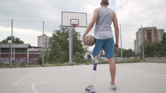 Back On Court Back shot of a male basketball player with prosthetic leg standing on the basketball court with a ball in his hand. amputee stock videos & royalty-free footage