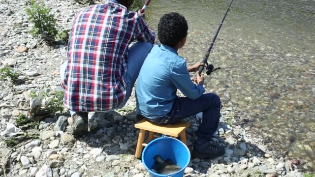 vídeos de stock e filmes b-roll de back portrait of little boy and his father fishing - fishman