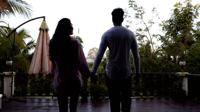 Back Rear View Of Coupe Walk On Summer Terrace Holding Hands Mix Race Man And Woman Looking At Morning Tropical Forest