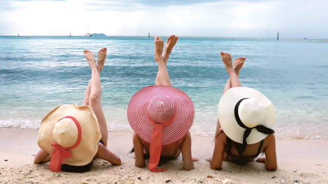 Back Rear View Of Three Girls Lying On Beach Raising Legs Back Rear View Of Three Girls Lying On Beach Raising Legs. sunbathing stock videos & royalty-free footage