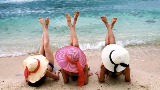 Back Rear View Of Three Girls Lying On Beach Raising Legs video