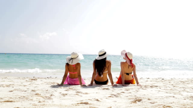 Back Rear View Of Three Girls On Beach In Bikini And Straw Hats Enjoy Sun Tan, Woman Tourists Group On Summer Holiday Back Rear View Of Three Girls On Beach In Bikini And Straw Hats Enjoy Sun Tan, Woman Tourists Group On Summer Holiday Slow Motion 60 sunbathing stock videos & royalty-free footage
