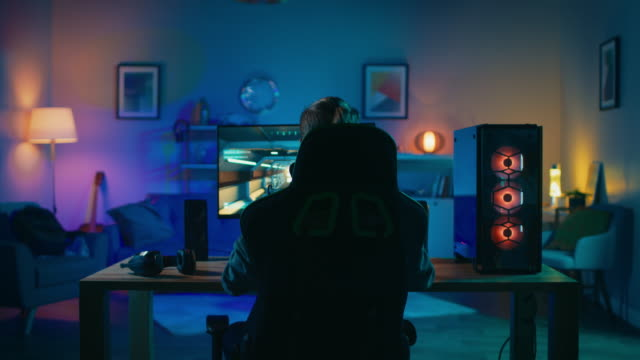 Back Shot of a Gamer Playing and Winning in First-Person Shooter Online Video Game on His Powerful Personal Computer. Room and PC have Colorful Neon Led Lights. Cozy Evening at Home.