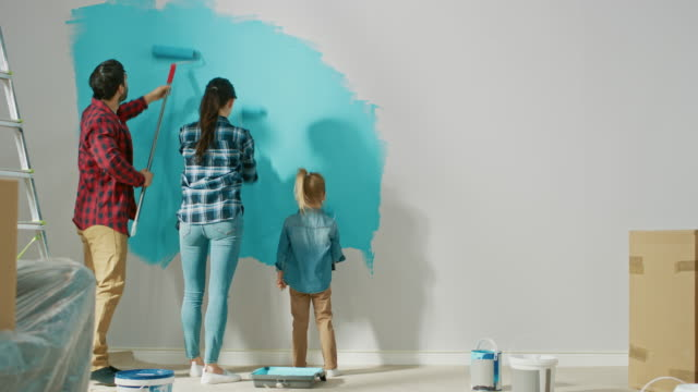 Back Shot of a Young Family Painting Walls with Their Cute Small Daughter. They Paint with Rollers that are Covered in Light Blue Paint. Room Renovations at Home.