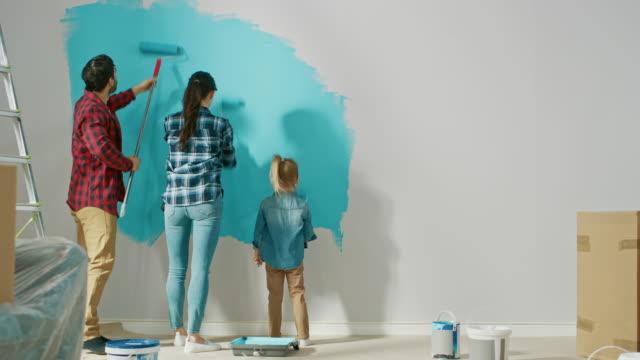 tillbaka skott av en ung familj målning väggar med sin söta lilla dotter. de måla med rullar som omfattas i ljus blå färg. rum renoveringar hemma. - painting wall bildbanksvideor och videomaterial från bakom kulisserna