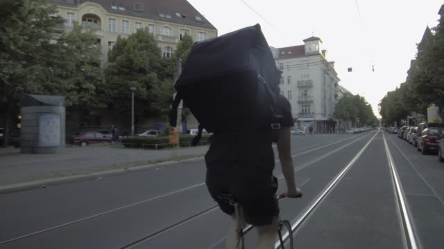 Back side view of food courier riding through the city