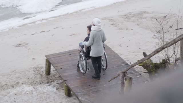 Back side view of young strong mother talking with son in wheelchair holding his shoulders. Caucasian disabled boy spending autumn day with mother on pier. Top view, wide shot.