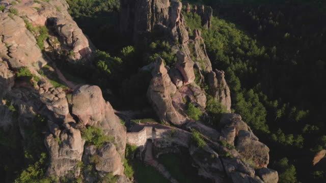 tillbaka till naturen. flygfoto över en turist vandring i de röda klipporna i belogradchik bergen. njutning utomhus en solig dag under covid-19 pandemin. unesco: s världsarvslista. - bulgarien bildbanksvideor och videomaterial från bakom kulisserna