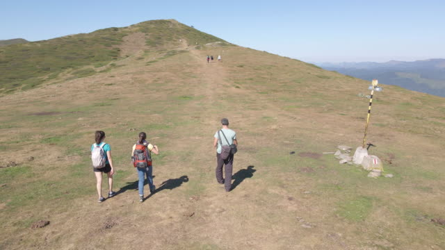 Back to Nature. Aerial view over group of tourists hiking in the high mountains during COVID-19 pandemic. Enjoyment outdoors on a sunny day.