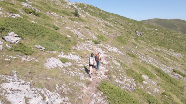 back to nature. aerial view over group of tourists hiking in the high mountains during covid-19 pandemic. enjoyment outdoors on a sunny day. - drone footage stock videos & royalty-free footage