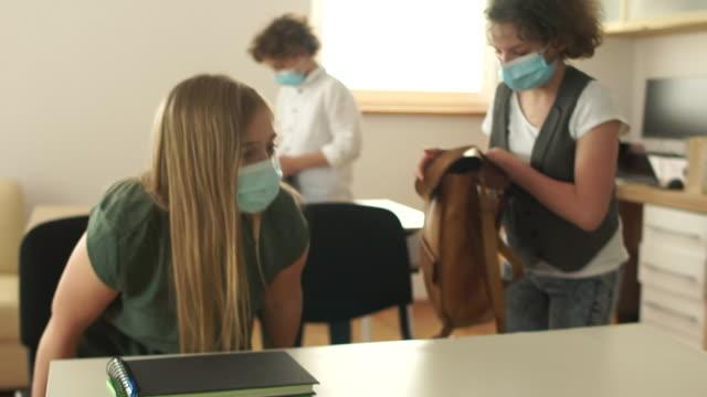 vidéos et rushes de retour à l'école après la quarantaine. les enfants masqués vont en classe et s'assoient à leur bureau. organisation du processus éducatif, nouvelles règles, vie après quarantaine - enfant masque