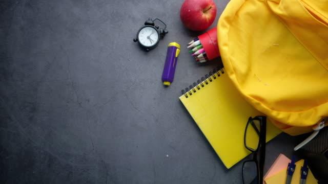 回到學校概念黃色背包和學校供應商在黑色背景。 - back to school 個影片檔及 b 捲影像