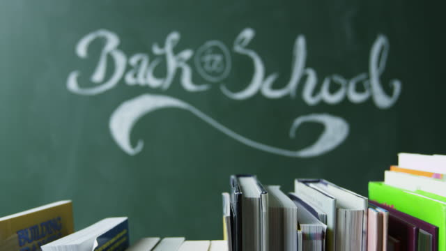 Back to school handwritten on chalkboard, books in foreground, shot on R3D video